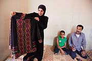Delal shows of some of her products. Delal and her husband and family at home. Delal walks along the narrow alleys to her temporary home in Shatila. She is a Palestinian from Damascus and now lives as a refugee in Shatila, a Palestinain camp in Beirut. She lives in Shatila with her extended family after they had to flee the war in Syria.