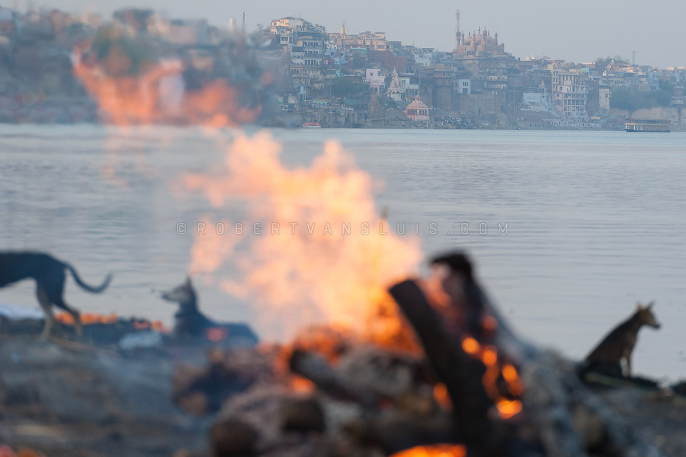 A funeral pyre burns at Harischandra cremation ground, with the city of Varanasi, India, in the background. Photo © robertvansluis.com
