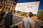 """22 OCTOBER 2011 - PHOENIX, AZ:    Occupy Phoenix protesters in Cesar Chavez Plaza in Phoenix. The demonstrations at Occupy Phoenix, AZ, entered their second week Saturday. About 50 people are staying in Cesar Chavez Plaza, in the heart of downtown. The crowd grows in the evening and on weekends. Protesters have coordinated their actions with police and have gotten permission from the city to set up shade shelters and sleep in the park, but without tents or sleeping bags, which is considered """"urban camping,"""" instead protesters are sleeping on the sidewalk.  PHOTO BY JACK KURTZ"""