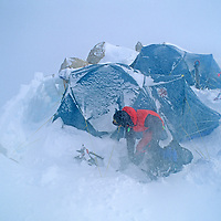 ANTARCTICA. Mountaineer (MR) digs out after during a blizzard at Camp Two during first ascent of 10,302-foot Mount Vaughan, near the South Pole. Later, winds blew over the snow walls and nearly crushed the tents.