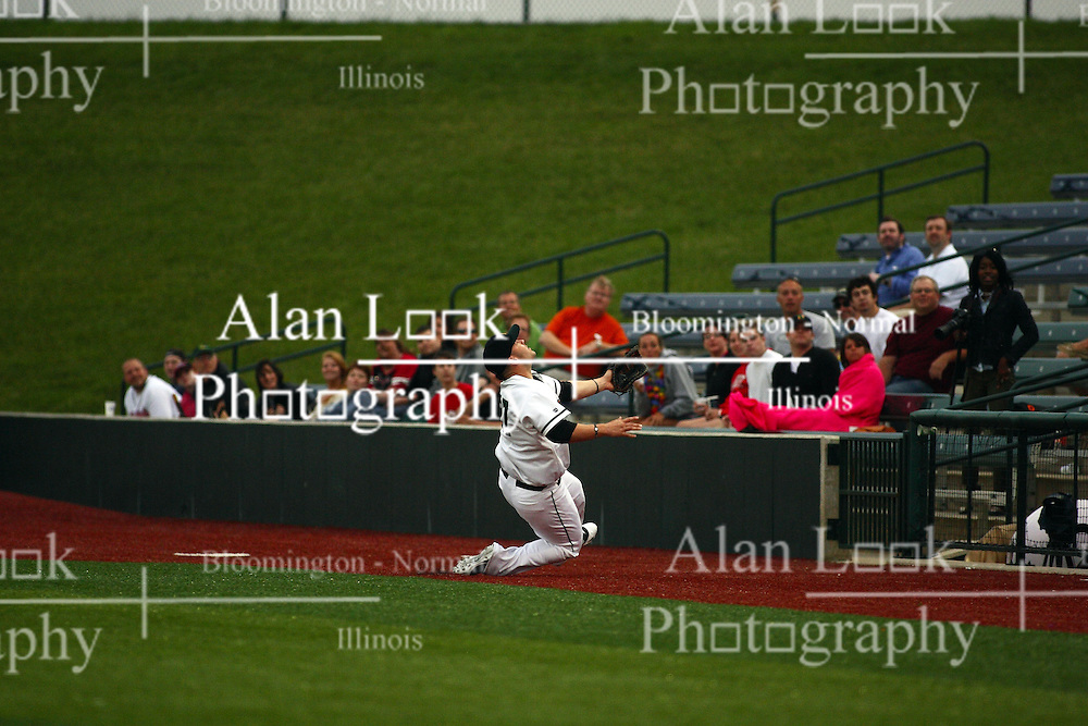 09 June 2011: First baseman Steve Alexander chases a high foul ball sliding into the dugout fence unable to make the grab during a game between the Lake Erie Crushers and the Normal Cornbelters at the Corn Crib in Normal Illinois.