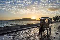 Cuba, Barracoa.  Bicycle taxi on Malecon at sunrise