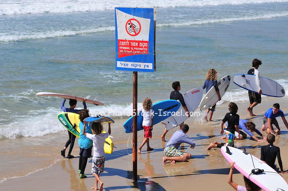 Israel, Haifa, summer activity on the beach Surfers enter the water