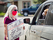 "26 APRIL 2020 - JEWELL, IOWA: A volunteer in Jewell thanks a motorist in Jewell Sunday who bought ""grab and go"" roast pork dinners during a fund raiser in the town. Jewell, a small community in central Iowa, became a food desert when the only grocery store in town closed in 2019. It served four communities within a 20 mile radius of Jewell. Some of the town's residents are trying to reopen the store, they are selling shares to form a co-op, and they hold regular fund raisers. Sunday, they served 550 ""grab and go"" pork roast dinners. They charged a free will donation for the dinners. Despite the state wide restriction on large gatherings because of the COVID-19 pandemic, the event drew hundreds of people, who stayed in their cars while volunteers wearing masks collected money and brought food out to them. Organizers say they've raised about $180,000 of their $225,000 goal and they hope to open the new grocery store before summer.            PHOTO BY JACK KURTZ"