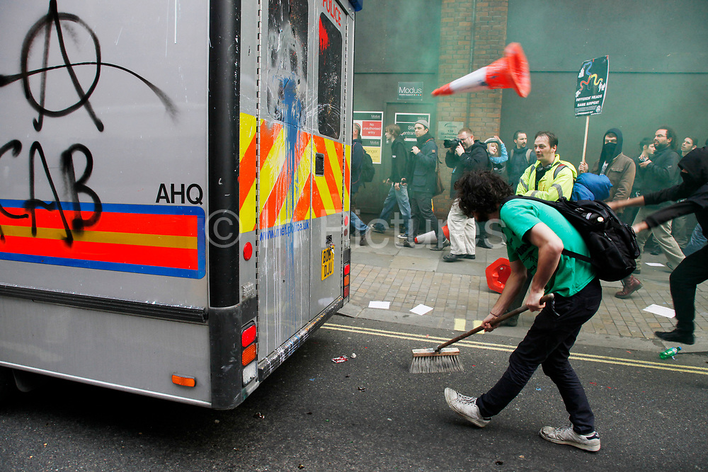 Protester pretending to sweep up during an attack on a police vehicle. Anti capitalists / anarchists go on the rampage through central London on the back of the peaceful TUC protest march. The masked demonstrators ran a twisting route through the capital confusing the police and creating a situation which was very difficult to manage. The protesters attacked banks, shops and hotels, and the police in riot gear fought  face to face with them as they were pelted with ammonia, paint and fireworks loaded with coins.
