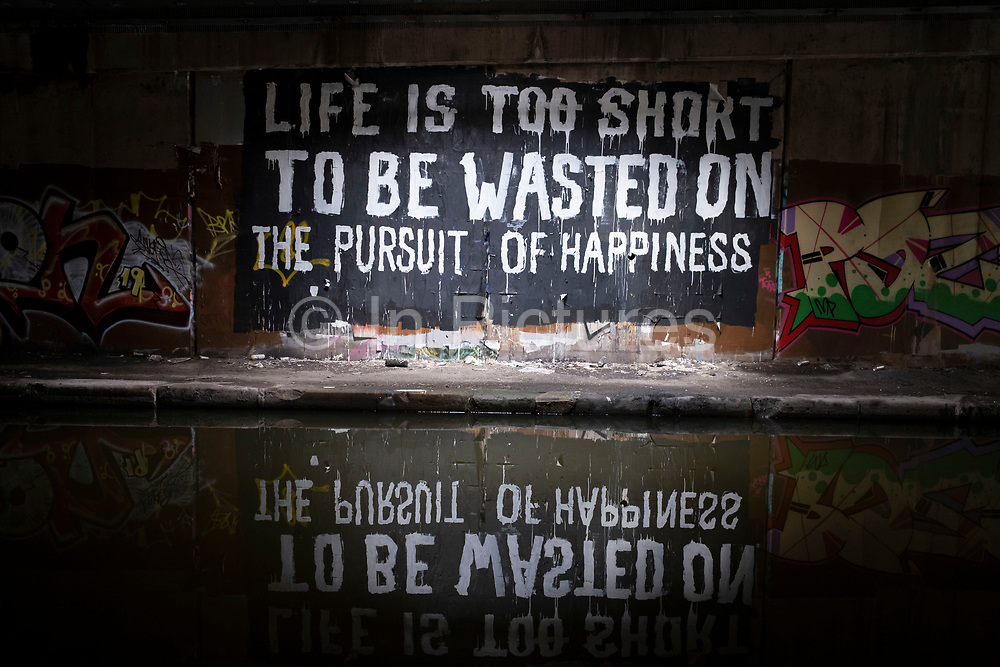 Life is too short to be wasted on the pursuit of happiness, a piece of poetic street art graffiti in the canal underpass at Gravelly Hill Interchange, aka Spaghetti Junction which is virtually deserted under Coronavirus lockdown, while far fewer vehicles pass overhead on 29th April 2020 in Birmingham, England, United Kingdom. The term Spaghetti Junction was originally used to refer to Gravelly Hill Interchange on the M6 motorway in an article published in the Birmingham Evening Mail on 1 June 1965 the journalist Roy Smith described plans for the junction as like a cross between a plate of spaghetti and an unsuccessful attempt at a Staffordshire knot. Coronavirus or Covid-19 is a new respiratory illness that has not previously been seen in humans. While much or Europe has been placed into lockdown, the UK government has put in place more stringent rules as part of their long term strategy, and in particular social distancing.