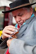 Male Brazilian Gaucho cowboy musician putting on cologne. Gaucho cowboy Rodeo, Flores de Cunha, Rio Grande do Sul.
