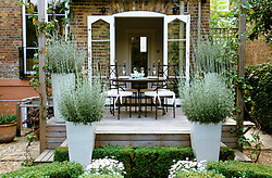 Raised deck seating and dining area surrounded by tall ceramic containers of Lavender - Lavandula dentata. Design: Anthony Goff