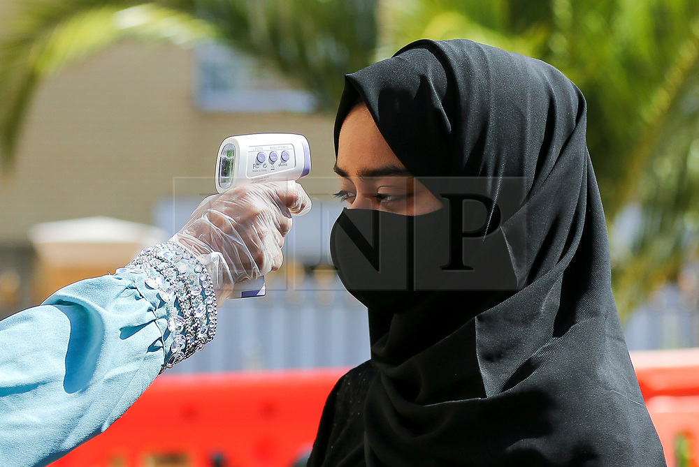 © Licensed to London News Pictures. 31/07/2020. London, UK. A worshipper's temperature is check at the entrance of Wightman Road Mosque, also known as London Islamic Cultural Society and Mosque, in north London as she arrives to pray and celebrate the festival of Eid. Last month the government announced that gatherings of more than 30 worshippers are allowed for acts of communal worship in churches, synagogues, mosques, temples and other places of worship. All worshippers attending Mosques for Eid celebrations have to wear face coverings and bring their own prayer mat, Quran, and a reusable shoe bag. Eid al-Adha, also called Eid Qurban or Bakra-Eid, is the second of two Islamic holidays celebrated worldwide each year, and considered the holier of the two. Photo credit: Dinendra Haria/LNP