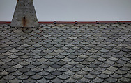 Scalloped tiles cover the roof of the Alnes fyr (lighthouse) on Godøy island Norway, visited on May 15, 2013. The lighthouse is known for its cakes at the adjacent cafe.   (© 2013 Cindi Christie)