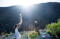 Two Wild Women parading with feathered poles the in desert nature wilderness.