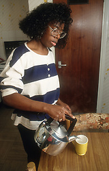 Woman making cup of tea in kitchen,