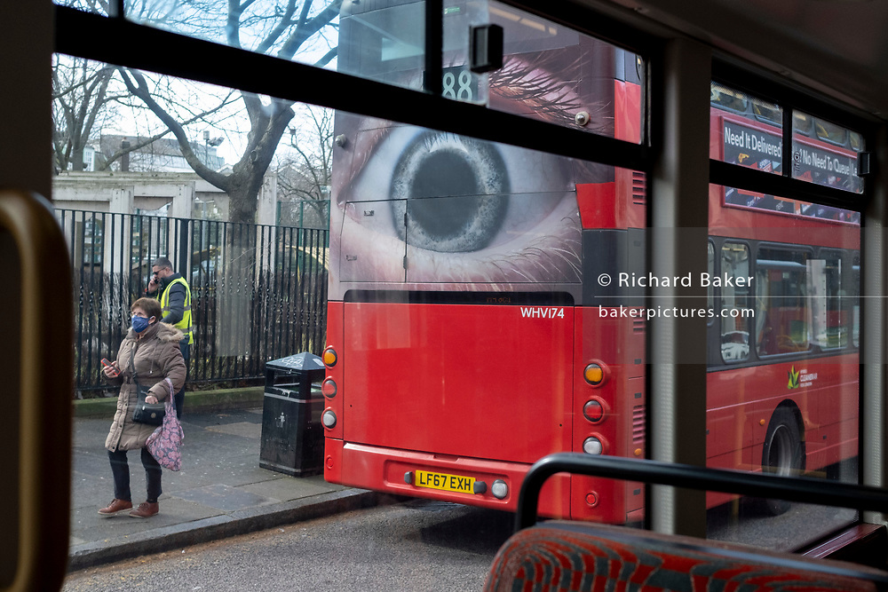A pedestrian passes a large eye on the rear of a London bus, which urges motorists to reduce their speeds on the capital's roads, on 11th March 2021, in London, England.