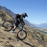 Andrew Bias from Auckland in action during the New Zealand South Island Downhill Cup Mountain Bike series held on The Remarkables face with a stunning backdrop of the Wakatipu Basin. 150 riders took part in the two day event. Queenstown, Otago, New Zealand. 9th January 2012. Photo Tim Clayton