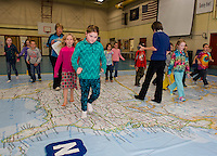 """Belmont Elementary second graders head """"East"""" on the interactive map with Phys Ed Teacher Mrs. Nims and Principal Sheila Arnold.  Each class will spend a period during the two days the map is in Belmont.  (Karen Bobotas/for the Laconia Daily Sun)"""