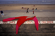 As families with children play on the sandy beach in the distance, a red wet suit dries on the sea wall, on 21st August 1992, in Scarborough, England.