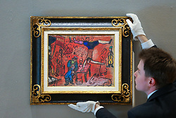 © Licensed to London News Pictures. 25/02/2019. London, UK. A technician hangs Autour de 'La Revolution 1937' painting, painted in the aftermath of the Second World War by the Russian-French artist Marc Chagall. Estimated at £300,000-500,000.<br /> Bonhams Impressionist and Modern Art Sale will take place in London on 28 February 2019. Photo credit: Dinendra Haria/LNP