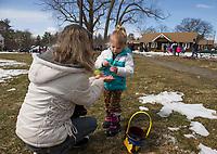 Paula Tarantino helps her granddaugher Layla Farrell open her Easter Egg found at the Leavitt Park Easter egg hunt on Sunday afternoon.  (Karen Bobotas/for the Laconia Daily Sun)
