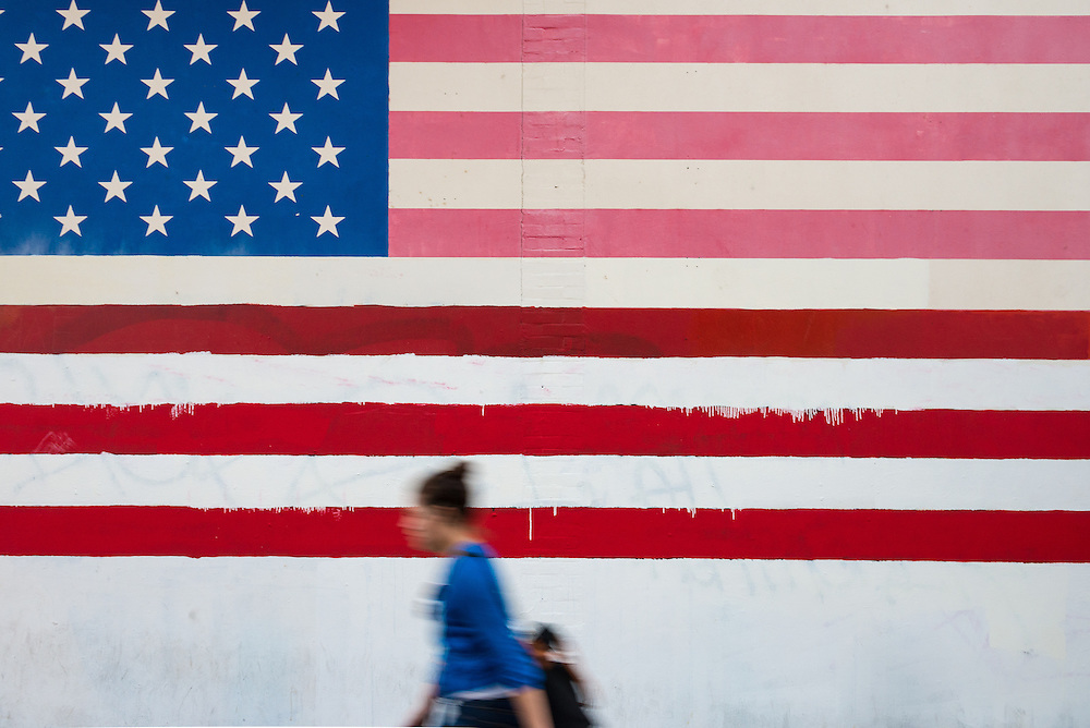 Pedestrians walking past a mural of United States flag in Chinatown, San Francisco