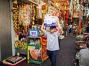 """17 FEBRUARY 2015 - BANGKOK, THAILAND: A man carries his shopping on his head past a store selling Chinese New Year supplies in Bangkok's Chinatown. Chinese New Year is February 19 in 2015. It marks the beginning of the Year of Sheep. The Sheep is the eighth sign in Chinese astrology and the number """"8"""" is considered to be a very lucky number. It symbolizes wisdom, fortune and prosperity. Ethnic Chinese make up nearly 15% of the Thai population. Chinese New Year (also called Tet or Lunar New Year) is widely celebrated in Thailand, especially in urban areas like Bangkok, Chiang Mai and Hat Yai that have large Chinese populations.       PHOTO BY JACK KURTZ"""