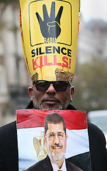 © Licensed to London News Pictures. 05/11/2015. London, UK. A man carries a photo of deposed Egyptian President Morsi during protests near Downing Street during the visit of Egyptian President Sisi. Photo credit: Peter Macdiarmid/LNP