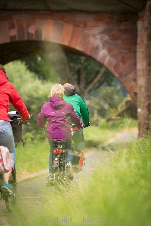 Three cyclists near stone bridge, Trier, Germany