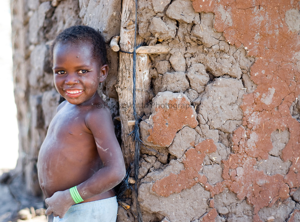 Young African boy next to mud house in village