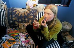 Teenage girl applying makeup in her bedroom UK
