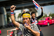 """20 DECEMBER 2013 - BANGKOK, THAILAND: An anti-government protestor chants """"Yingluck Get Out!"""" on Silom Road. Thousands of anti-government protestors, supporters of the so called Peoples Democratic Reform Committee (PRDC), jammed the Silom area, the """"Wall Street"""" of Bangkok, Friday as a part of the ongoing protests against the caretaker government of Yingluck Shinawatra. Yingluck dissolved the Thai Parliament earlier this month and called for national elections on Feb. 2, 2014. The protestors want the elections postponed and the caretaker government to step down. The Thai election commission ruled Friday that the election would go on dispite the protests.          PHOTO BY JACK KURTZ"""