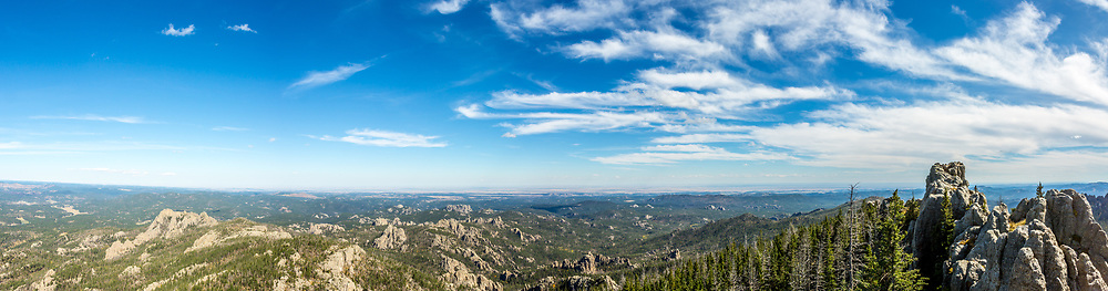 Panoramic view looking east from Black Elk Peak. Backside of Mount Rushmore is visible in the distance. Rushmore is just left of center, the table rock formation. Imagine a straight line down from the end of the cloud sweep. The backside of Rushmore is the rock formation just below the horizon. See next photo. Panorama Photos taken September 30, 2017.