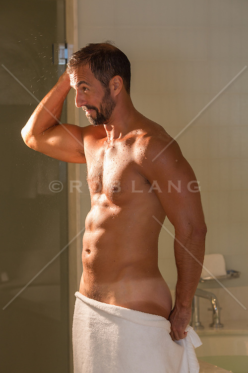 Latin man in the bathroom with a towel in looking in the mirror