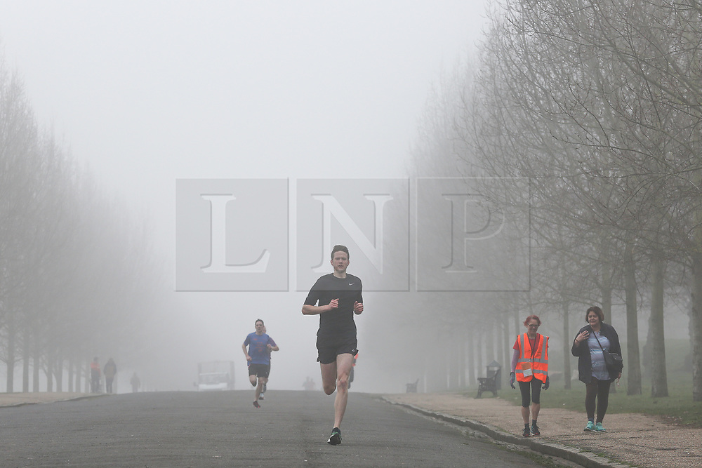 © Licensed to London News Pictures. 23/02/2019. London, UK. Park runners running in thick fog in Finsbury Park, north London. According to the Met Office London's temperatures is likely to reach 15 degrees celsius and UK could break records this weekend, with high pressure from Europe bringing dry and sunny weather. Photo credit: Dinendra Haria/LNP