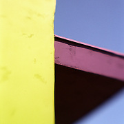 Brightly colored detail of yellow building wall and purple canopy against deep blue sky.