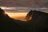 Evening sunlight shines across Helvetestind mountain peak and Bunes beach, Moskenesøy, Lofoten Islands, Norway