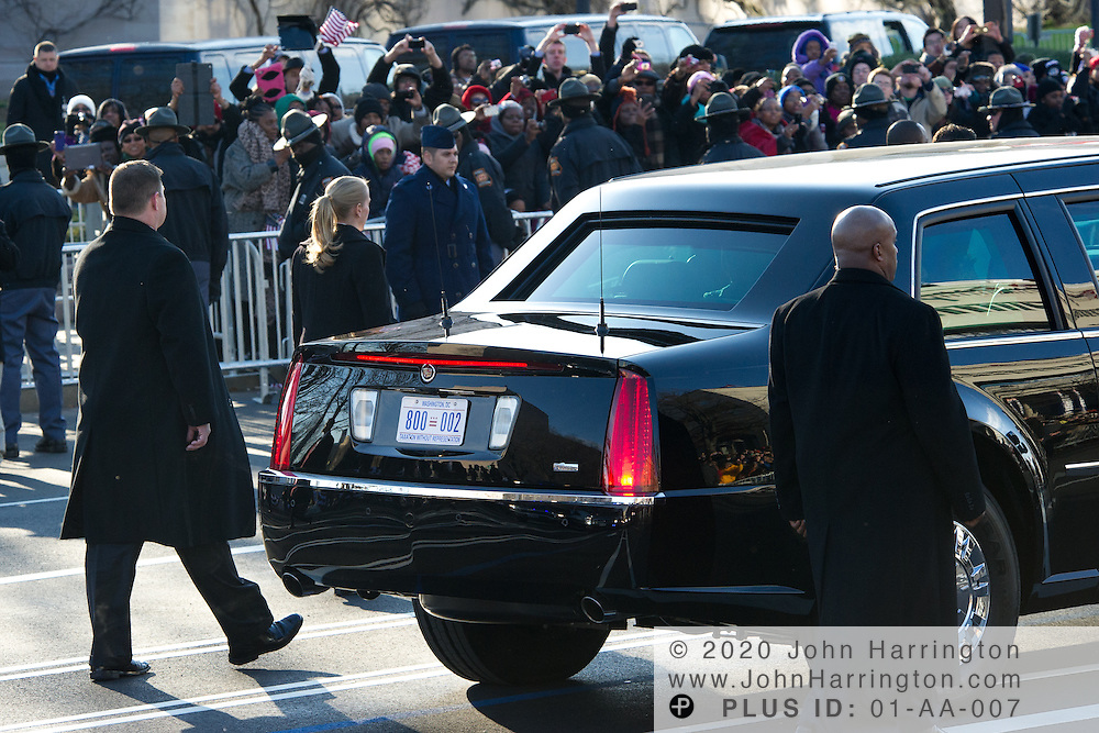 "The presidential limousine displaying a Washington DC license plate reading ""Taxation without Representation"" is guarded along the parade route by members of the United States Secret Service, including a notable female agent with a blonde ponytail during the 57th Presidential Inauguration of President Barack Obama at the U.S. Capitol Building in Washington, DC January 21, 2013."