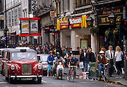 Traffic, cyclists and pedestrians fill this busy urban landscape in Oxford Street in London's west end. As the cars drive past allowing for the space needed for the bikes and their riders, shoppers walking on the pavement (sidewalk) make their way to see the shops and stores. We see the signage of McDonalds, Virgin and Sock Shop - all major brands in the early 1990s - plus Cannon cinemas. There is boxes litter in the gutter which the cyclists have to steer past and they pass-by.