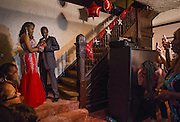 Jerlan Payne looks for some guidance in attaching a boutonniere to her date Alex Watt on the stairs of her Bronzeville home during while family and friends take photos at her prom send-off party Friday, May 23, 2014. (Brian Cassella/Chicago Tribune) B583716573Z.1 <br /> ....OUTSIDE TRIBUNE CO.- NO MAGS,  NO SALES, NO INTERNET, NO TV, CHICAGO OUT, NO DIGITAL MANIPULATION...