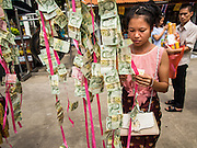 11 JULY 2014 - BANGKOK, THAILAND:  A Thai woman makes merit by donating money at Wat Mahabut for Asalha Puja Day. Asalha Puja is the day the Lord Buddha preached his first sermon to followers after attaining enlightenment. The day is usually celebrated by merit making and listening to a monks' sermons. It is also day before the start of the Rains Retreat, the three month period when monks stay in their temple for intense mediation and spiritual renewal.   PHOTO BY JACK KURTZ