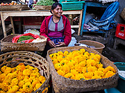 07 AUGUST 2017 - BEBANDEM, BALI, INDONESIA: A woman sells marigolds in the market in Bebandem, in far eastern Bali. The market is known for baskets, which are woven in the area. Bali's local markets are open on an every three day rotating schedule because venders travel from town to town. Before modern refrigeration and convenience stores became common place on Bali, markets were thriving community gatherings. Fewer people shop at markets now as more and more consumers go to convenience stores and more families have refrigerators.     PHOTO BY JACK KURTZ