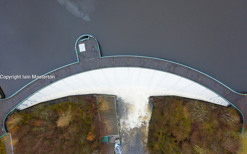 Glen Devon, Perth and Kinross, Scotland, UK. 20 Feb 2021. Meltwater from recent snow and heavy rain has filled Scottish reservoirs to capacity. Dam spillways are now full whilst discharging water downstream. Pic; Drone image of spillway at Castlehill Dam running at full capacity to discharge water from the reservoir. Iain Masterton/Alamy Live News