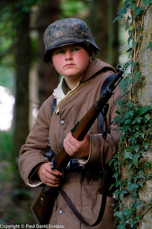 Reenactor dressed in late War German winter clothing wearing a splinter pattern camouflage Parka and Steel helmet, Short Boots and Gaiters carrying the Mauser K98 Rifle. <br /> <br />  September 2019<br /> All Images Copyright Paul David Drabble - <br /> All rights Reserved - <br /> Moral Rights Asserted -
