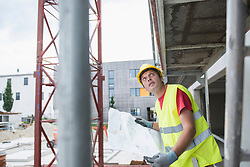 Construction worker holding blueprint at construction site, Munich, Bavaria, Germany