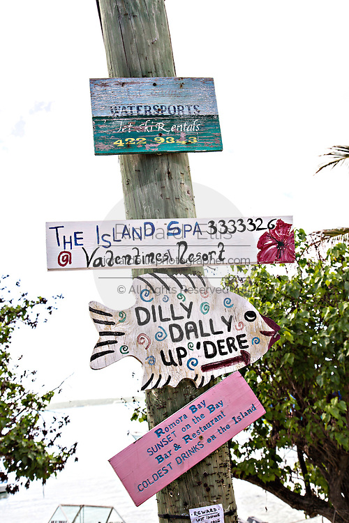 Directional signs on a telephone pole in Dunmore Town, Harbour Island, The Bahamas