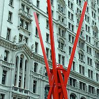 Red modern sculpture meets historic facade