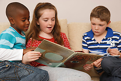 White girl reading to two boys