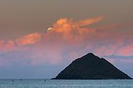 Full moon rising over Moku Iki, one of the Mokulua Islands, Lanikai Beach, Kailua Bay, Oahu, Hawaii
