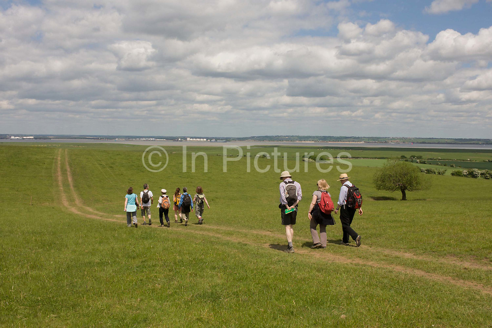 A group of country ramblers walk down a slope of grassland near Halstow on the Kent Thames estuary marshes, potentially threatened by the future London airport. In small groups, the friends descend the slop towards the river beyond. With the panoramic views the landscape could controversially become the site for London's estuary airport, built on reclaimed and marshland on the river Thames, east of the city. Current London mayor Boris Johnson is in faviour of this project to alleviate pressure from other airport hubs, regardless of wildlife (especially a nearby protected bird sanctuary).