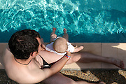 father with baby at the edge of the swimming pool