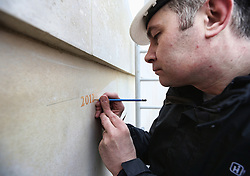 © Licensed to London News Pictures. 08/04/2013. National Memorial Arboretum, UK.  The painstaking process of engraving the names of UK Servicemen and women who were killed on duty or through terrorism in 2012 started today at the National Memorial Arboretum.  The engraver, Nick Hindle set to work with his pencil to mark out the 2012 start to the wall.  Photo credit: Alison Baskerville/LNP