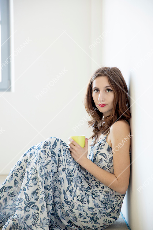 Sitting woman with a cup of tea in her hand